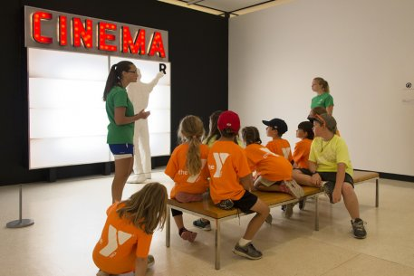 A docent discusses George Segal's Cinema with students from the YMCA
